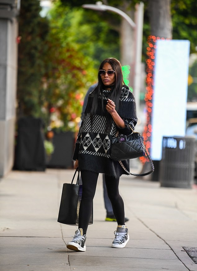 Naomi Campbell donning chunky grey leather ankle high top sneakers