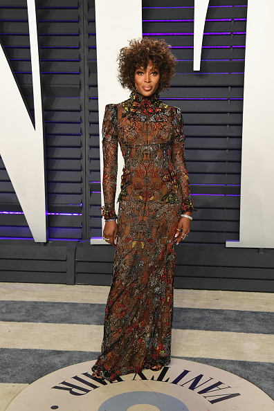 Naomi Campbell wearing a formfitting brown gown with a lace detailing fabric, full sleeves, padded shoulder, embroidered, a turtleneck and flared hem