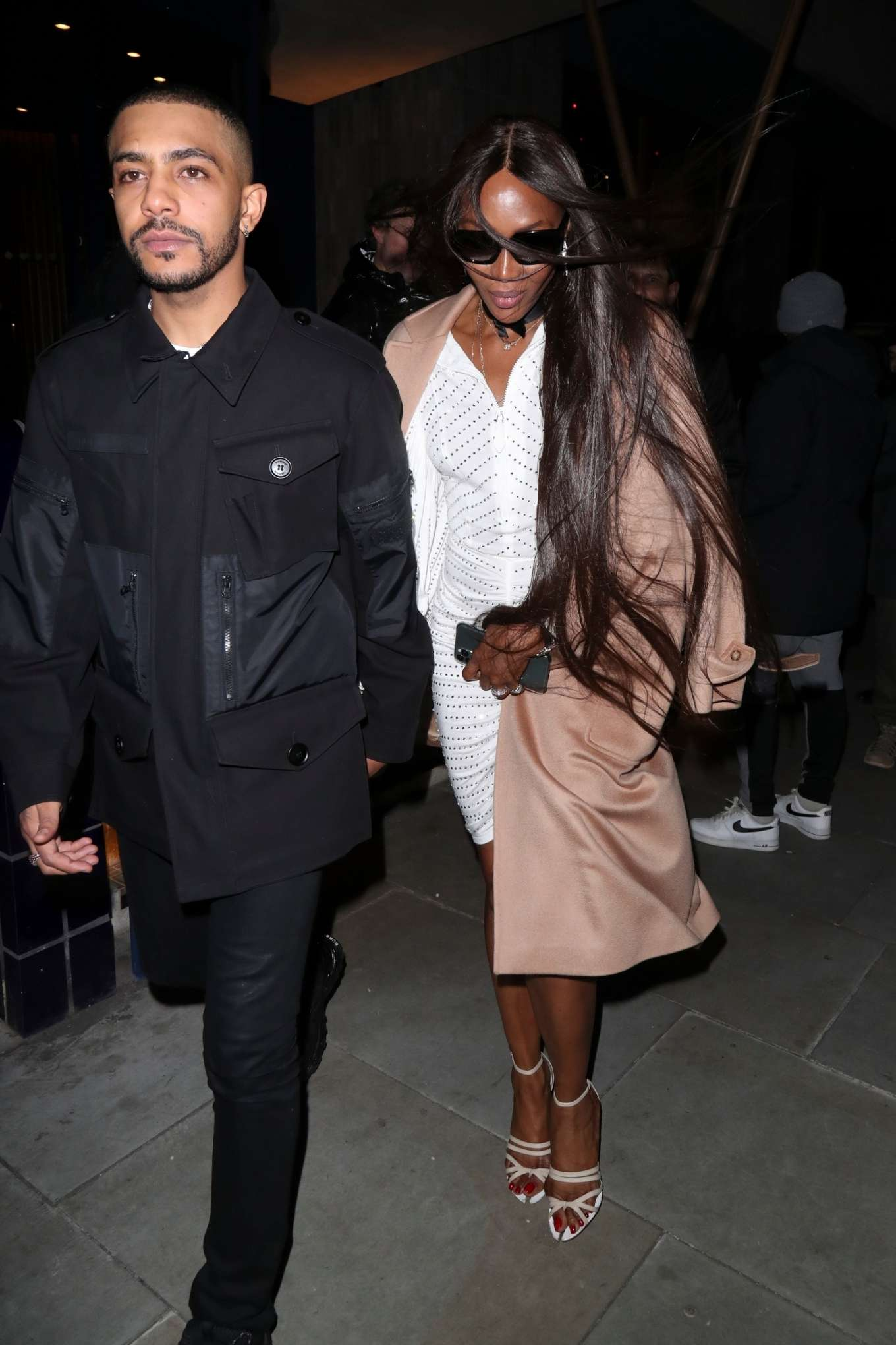 Naomi Campbell donning a cream open front cashmere coat with full sleeves