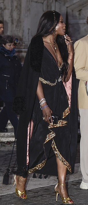 Naomi Campbell wearing a Plunging draped satin black dress with a satin material, asymmetric design, cinched waist and asymmetric hem