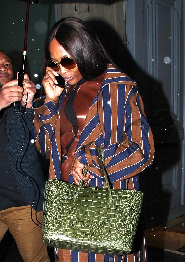 Naomi Campbell rocking a brown tucked in sweater with a soft leather fabric and a turtleneck