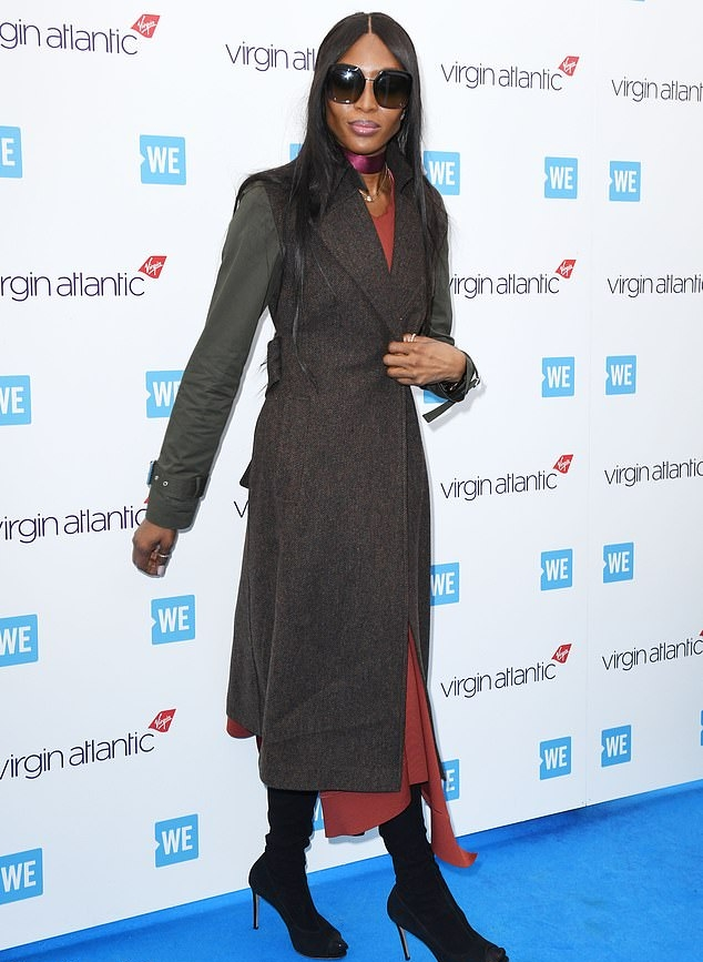 Naomi Campbell wearing narrow black suede mid calf boots with high heel