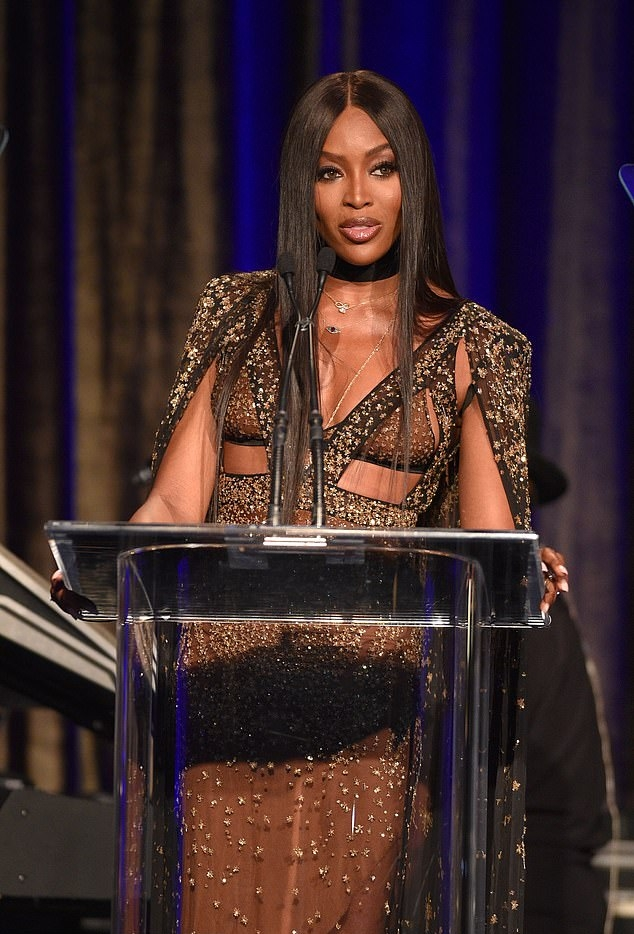 Naomi Campbell wearing black open toe sandals with ice pick heel and wide strap