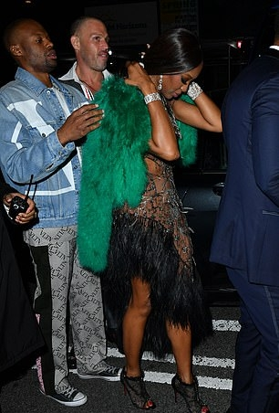 Naomi Campbell rocking a Voluminous shiny sea green fur jacket with a fur material, full sleeves and feather bolero
