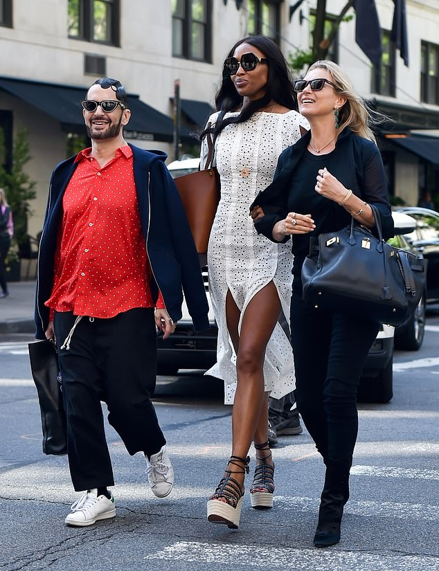 Naomi Campbell rocking strappy black cream crisscross tie wedges with platform heels and thin straps