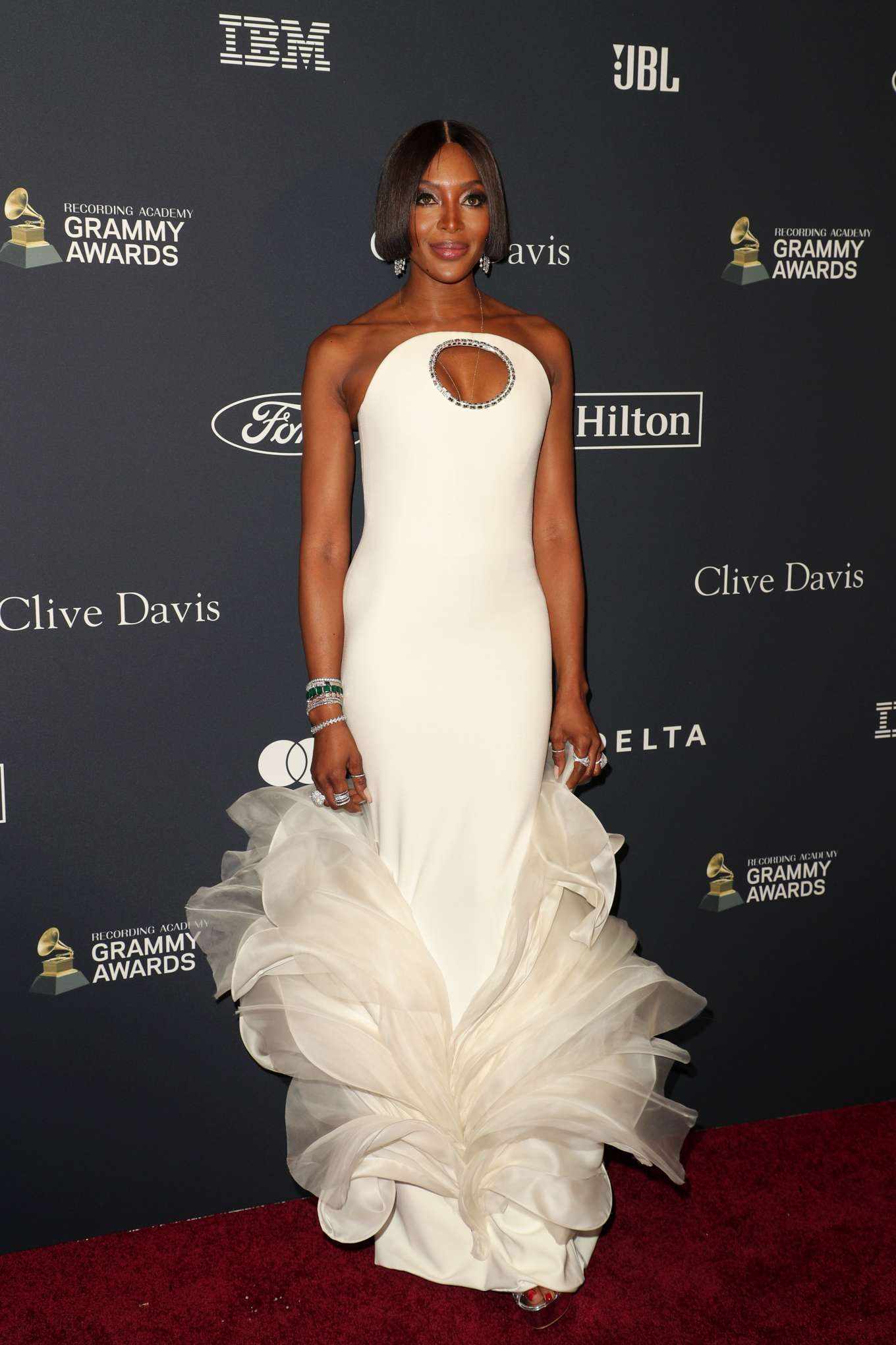 Naomi Campbell rocking a formfitting white gown with crystal embellished, a asymetrical neckline and ruffled hem