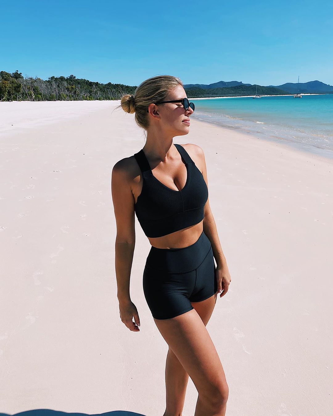 Natasha Oakley donning a Black Alo Yoga bralette with criss cross back, a V-neck and wide strap