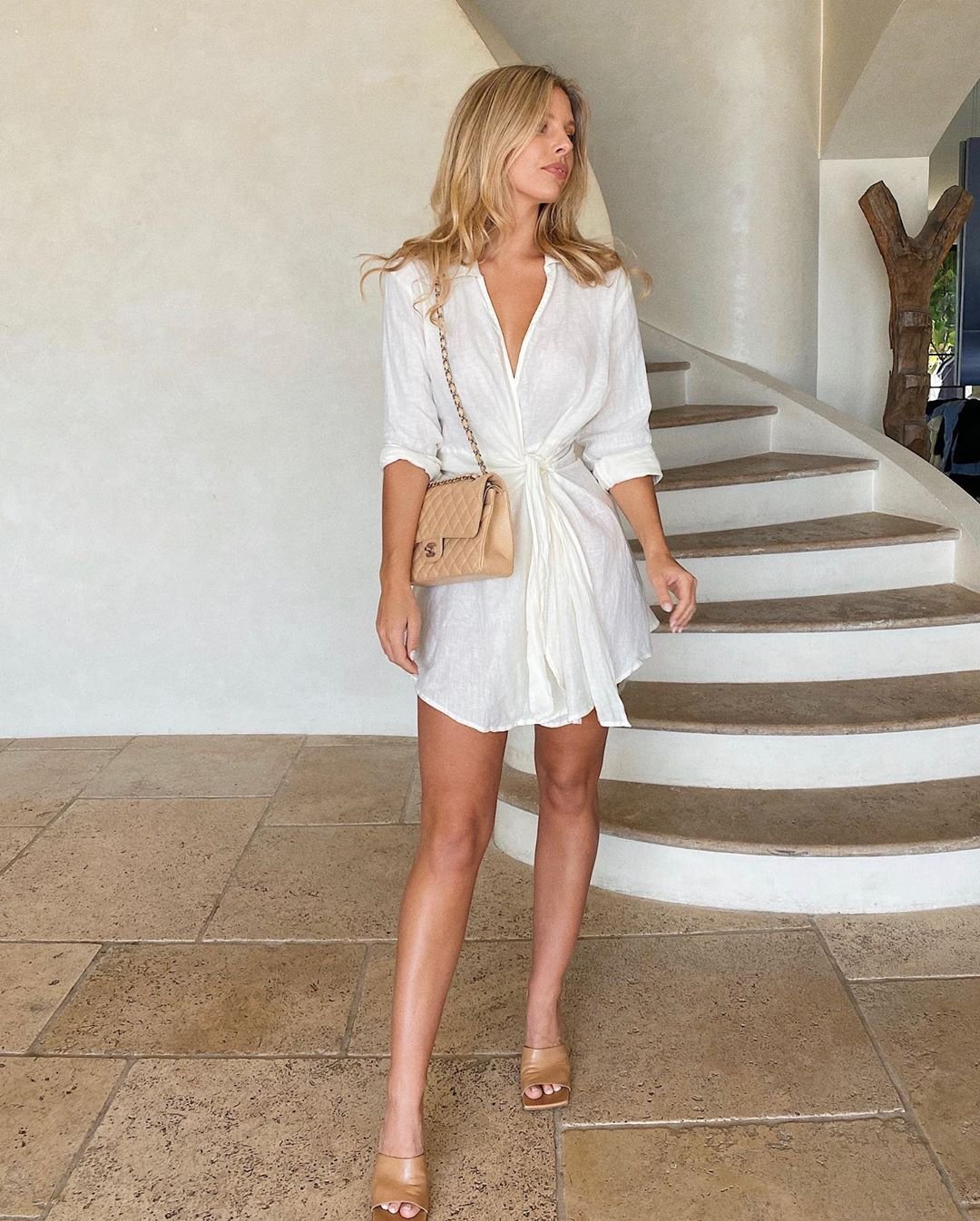 Natasha Oakley rocking a Ivory linen Monday Swimwear mini dress with a linen fabric, 3/4 sleeves, a V-neck, cinched waist and curved hem