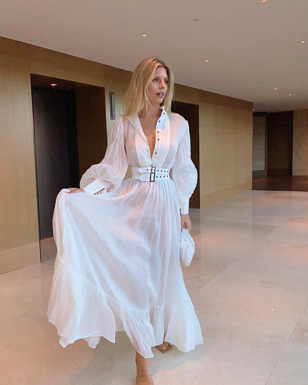 Natasha Oakley donning a See through white Leo and Lin maxi dress with a see-through linen material, puffy sleeves, wide cuffs, button front, cinched waist and flared hem