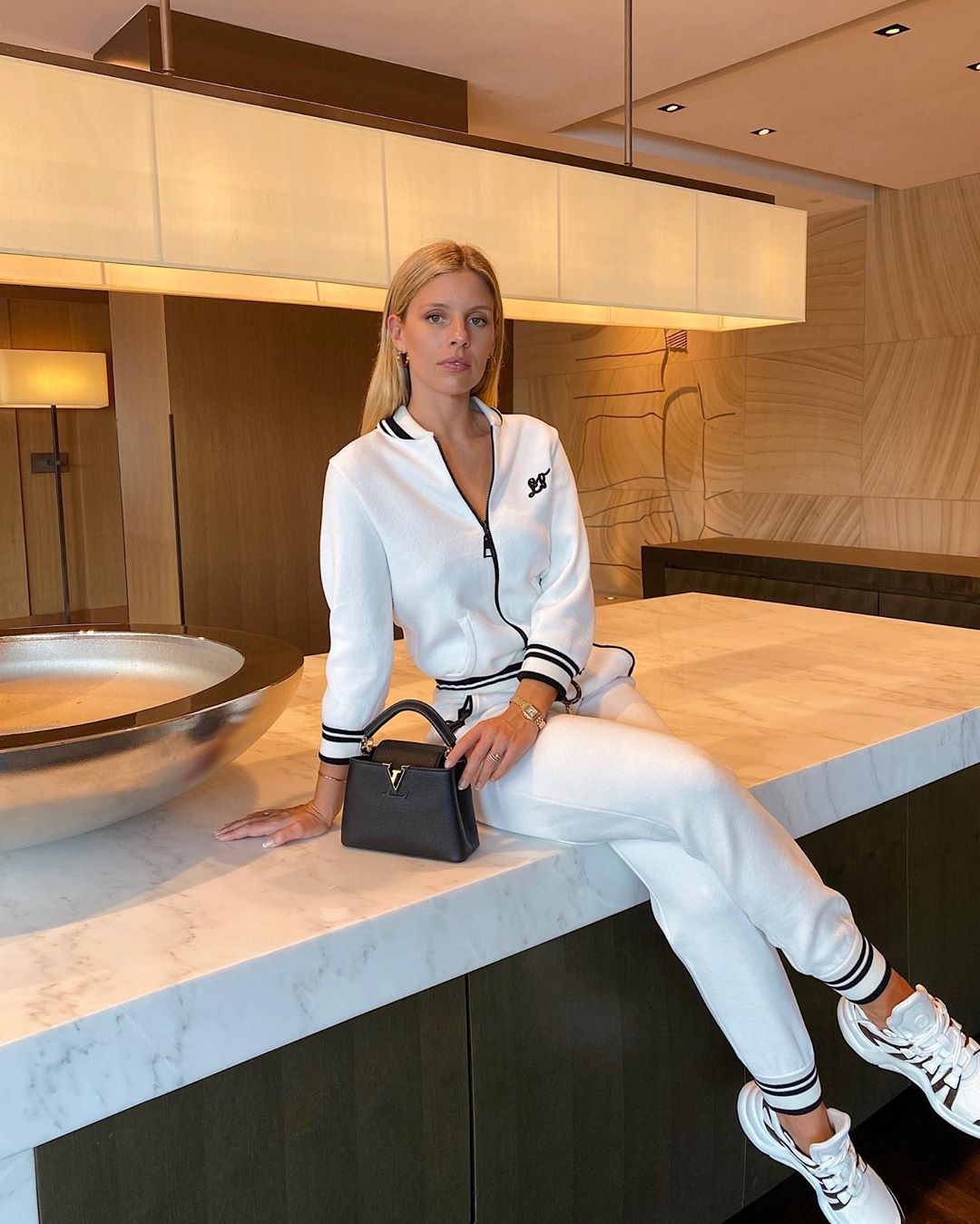 Natasha Oakley donning a Sportswear inspired white black striped Louis Vuitton jacket with full sleeves, baseball collar and black striped