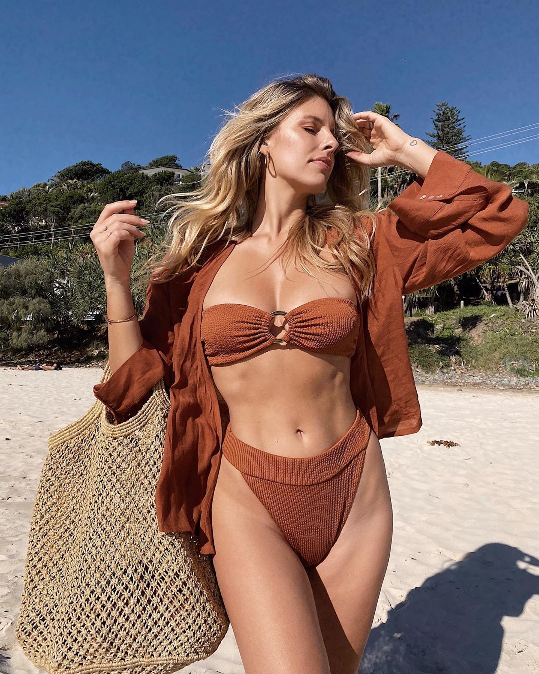 Natasha Oakley donning a Skimpy clay Monday Swimwear bikini top with metal detailing and a very low cut sweetheart neckline