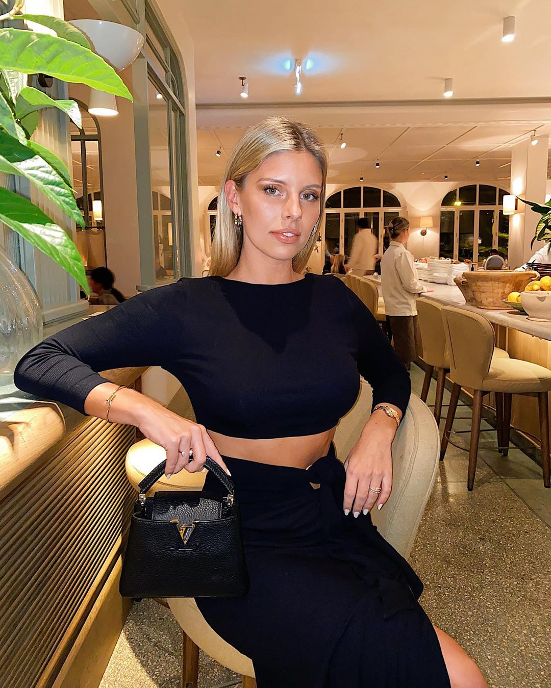 Natasha Oakley donning a Figure hugging Song Of Style black crop top with 3/4 sleeves and a crew neck