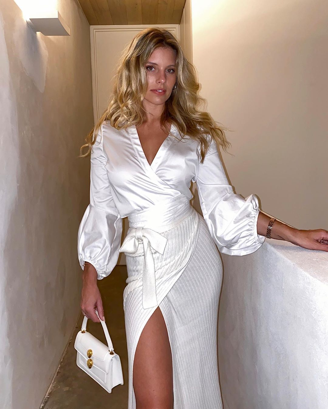Natasha Oakley rocking a Shiny white satin wrap top with a satin material, puffy sleeves and a V-neck