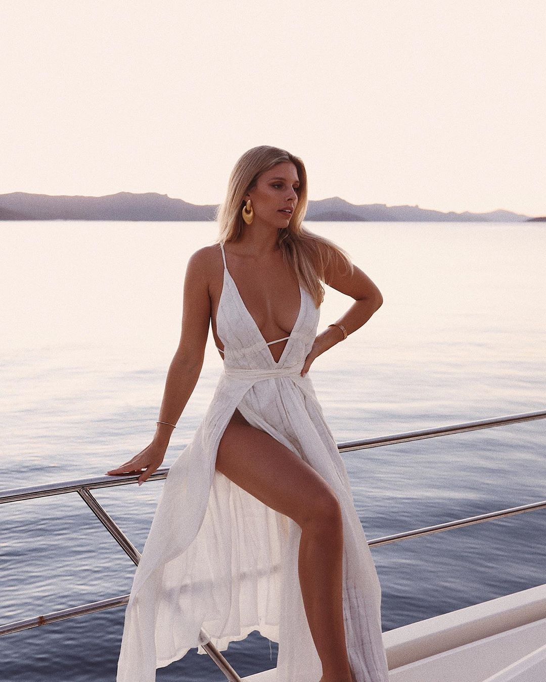 Natasha Oakley rocking a Off white Cult Gaia maxi dress with a linen material, spaghetti straps, cinched waist and flared hem