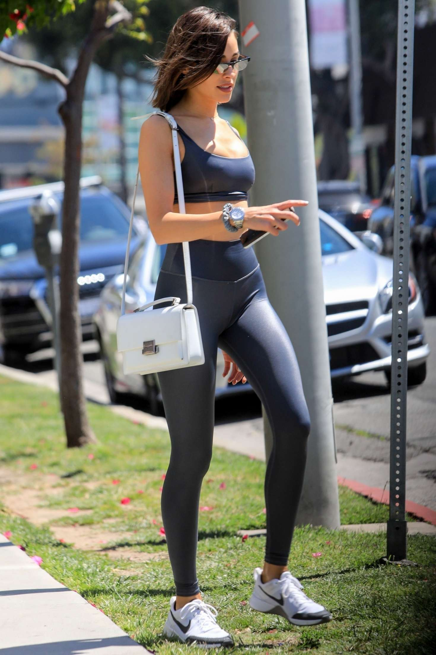 Olivia Culpo donning shiny black Alo skinny leggings with a spandex fabric