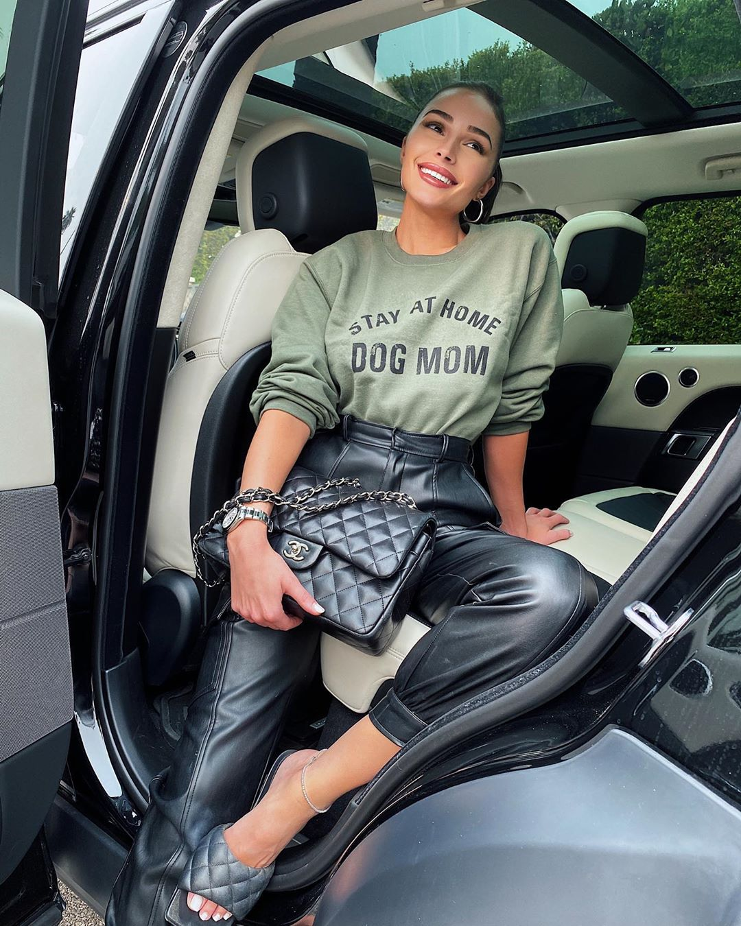 Olivia Culpo wearing baggy black leather high rise ankle length trousers with side pockets
