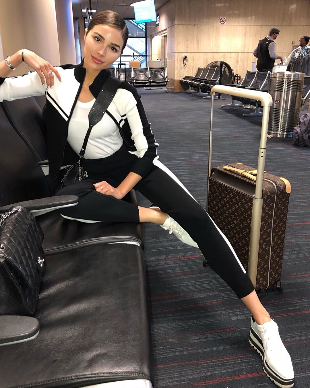 Olivia Culpo donning relaxed fit black cropped ankle length track pants with ribbed hem with side-stripes