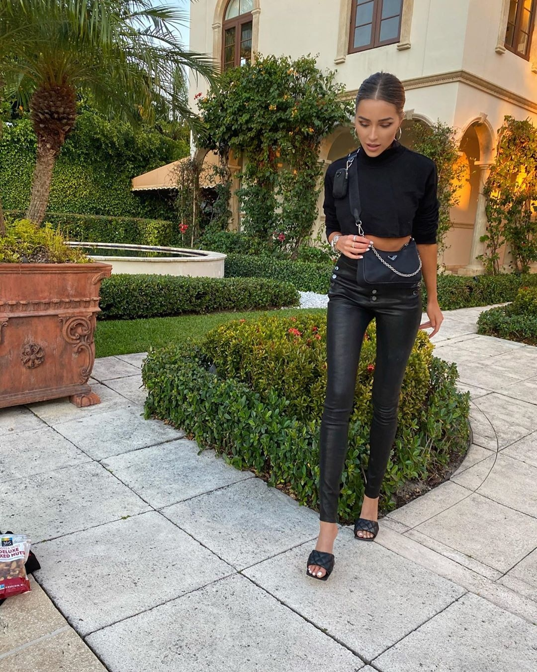 Olivia Culpo donning narrow fit black leather button front pants