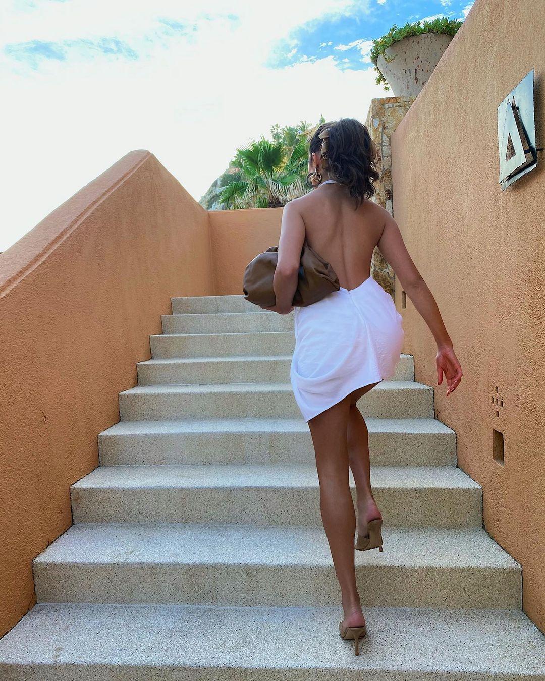 Olivia Culpo rocking a White Jacquemus cotton halter mini dress with a cotton fabric, strappy, a halter neck and asymmetric hem
