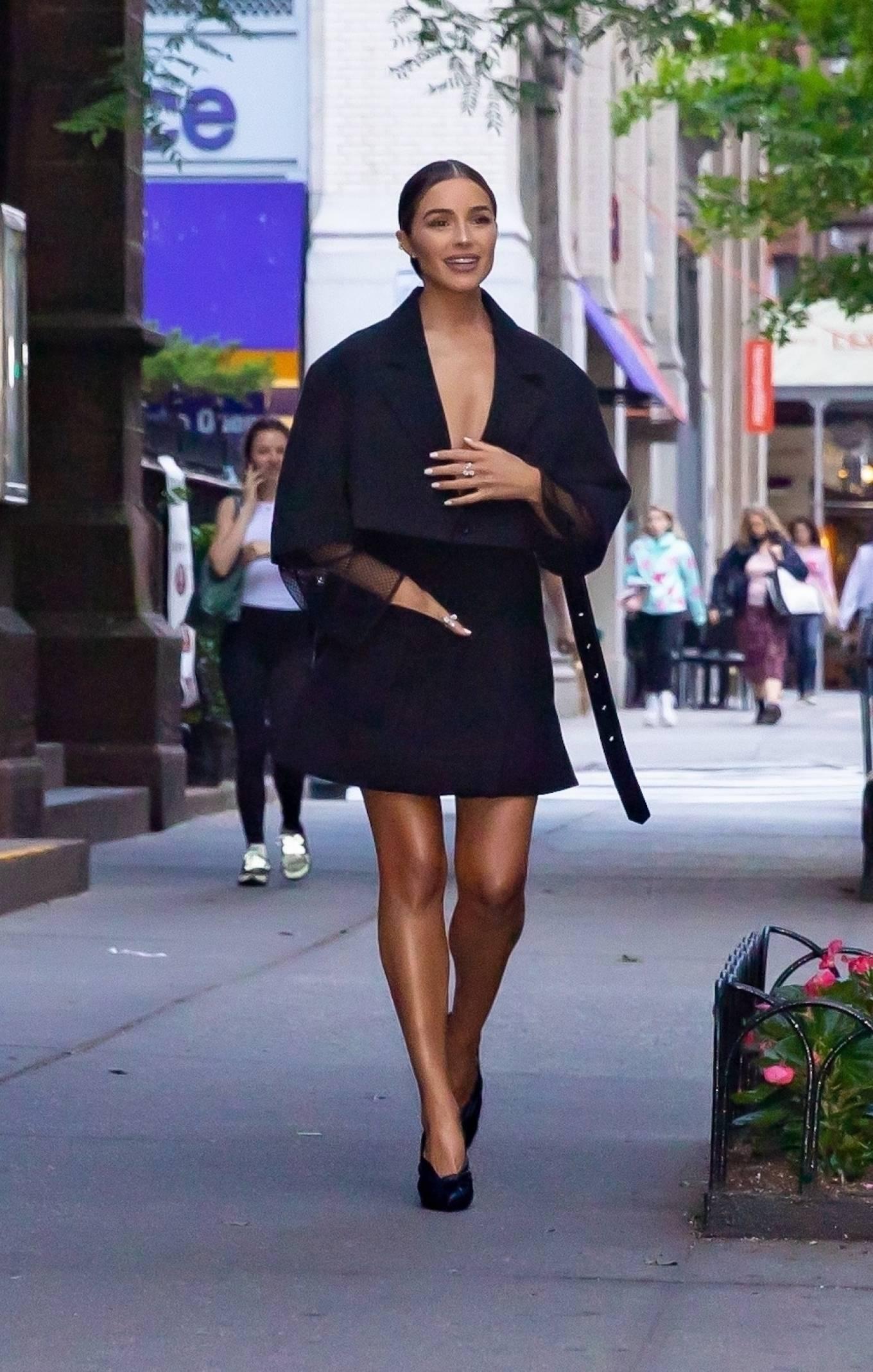 Olivia Culpo, black pumps, black Louis Vuitton crop jacket, pointed, slip on, stiletto heels, black wrap skirt. Olivia Culpo donning pointed black slip on pumps with stiletto heels and twisted front detailing