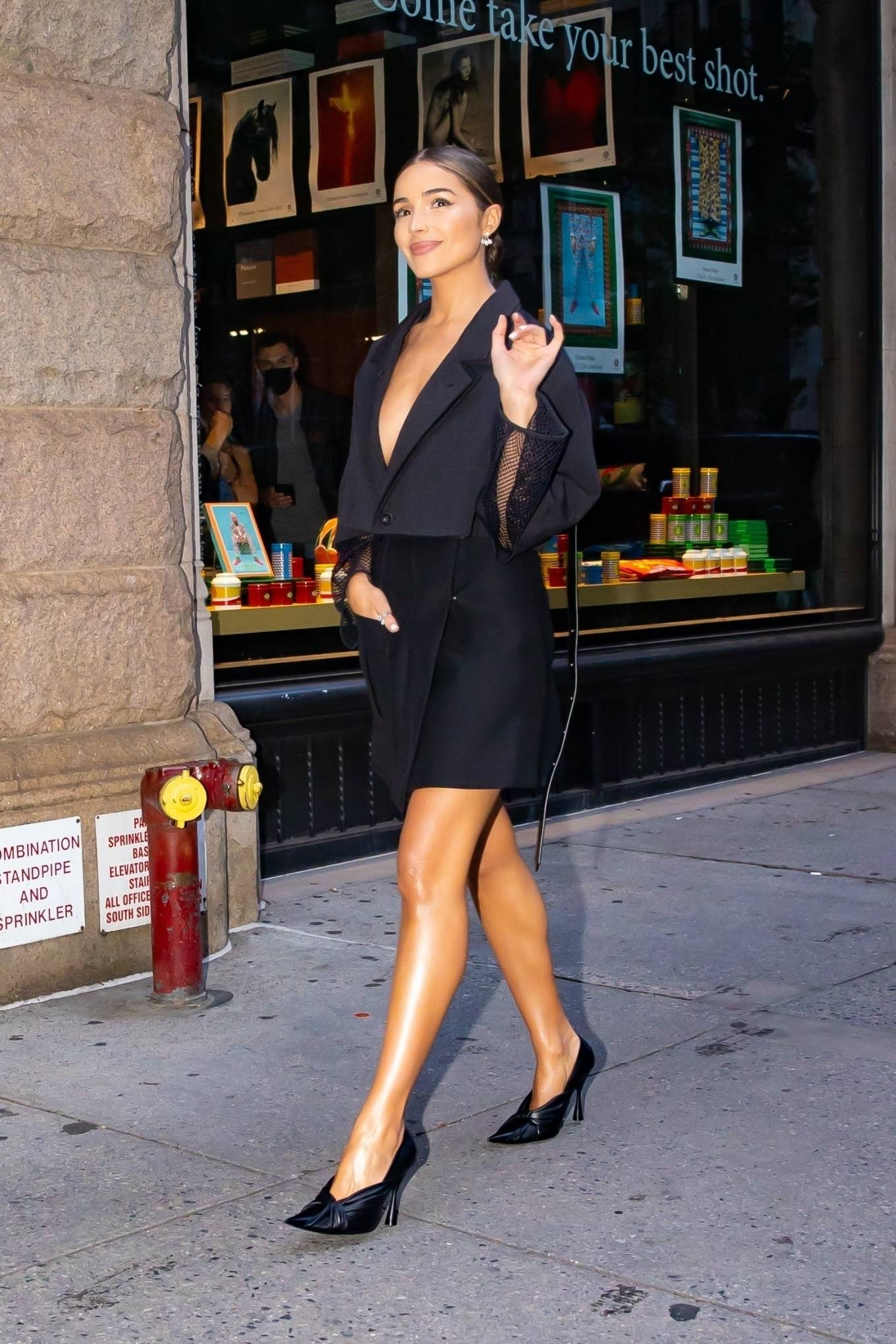 Olivia Culpo, black pumps, black Louis Vuitton crop jacket, pointed, slip on, stiletto heels. Olivia Culpo donning pointed black slip on pumps with stiletto heels and twisted front detailing
