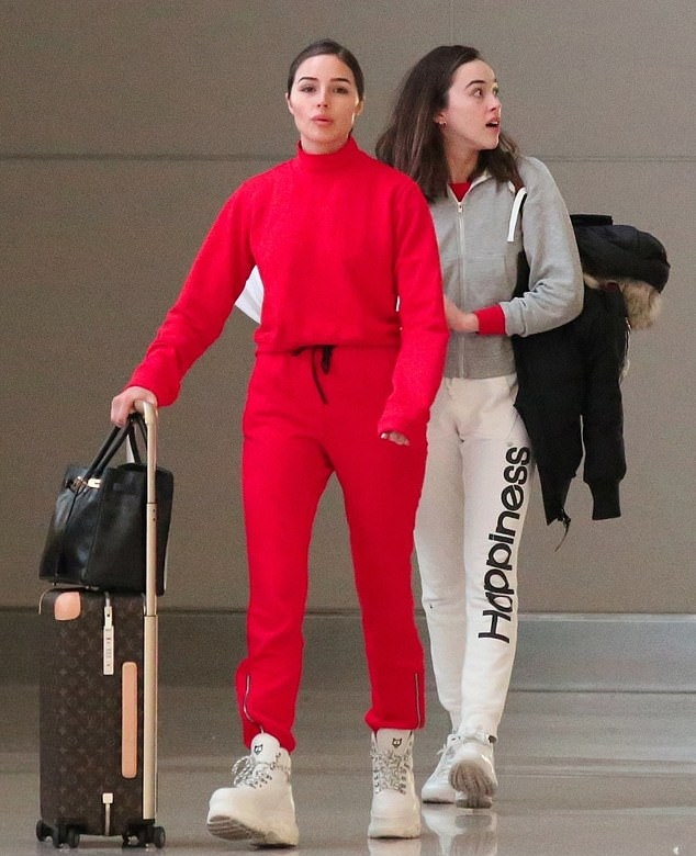 Olivia Culpo wearing bright red baggy track pants with zipper accents