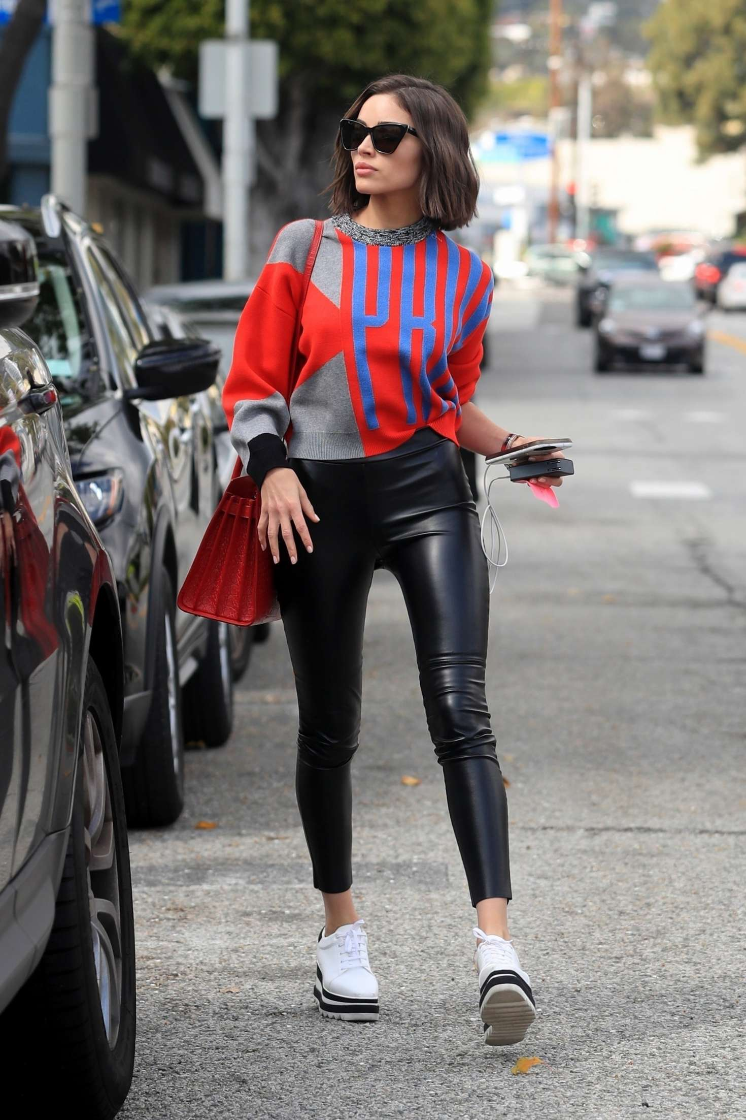Olivia Culpo wearing cropped black leather ankle length jeans with high rise