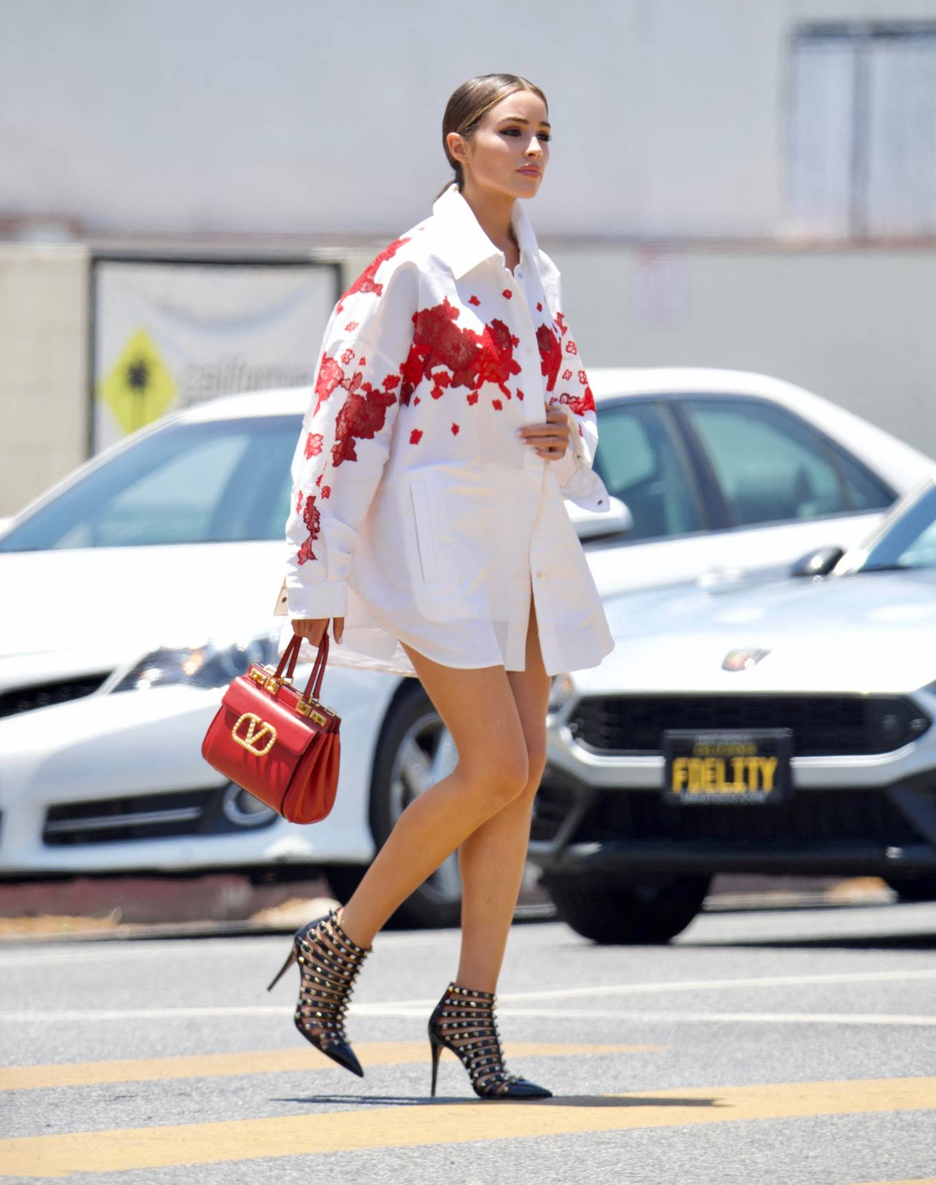 Olivia Culpo rocking studded black leather ankle boots by Valentino with stiletto heels and buckle