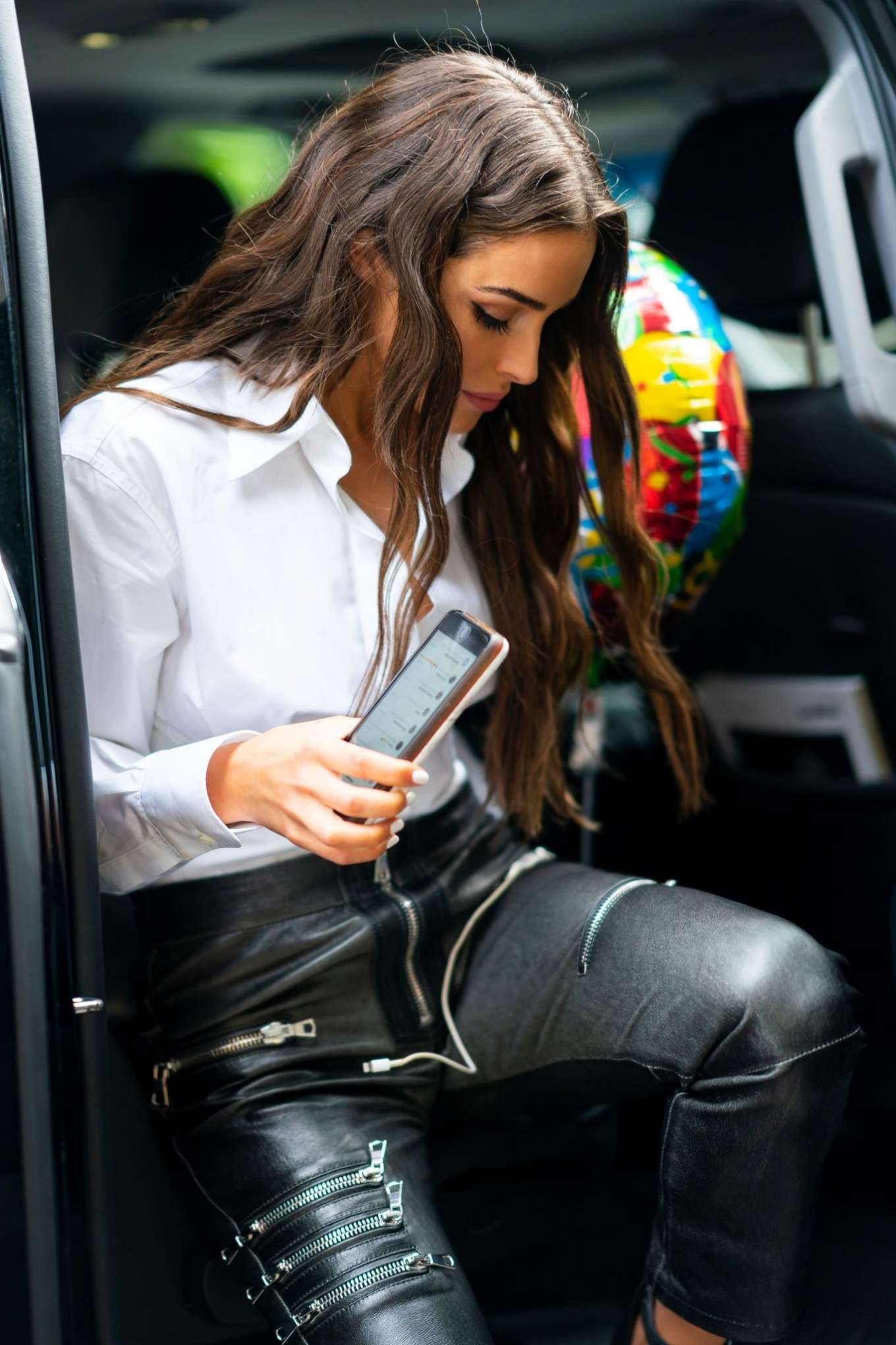 Olivia Culpo wearing Straight fit black leather high rise jeans with zipper accents and a leather fabric