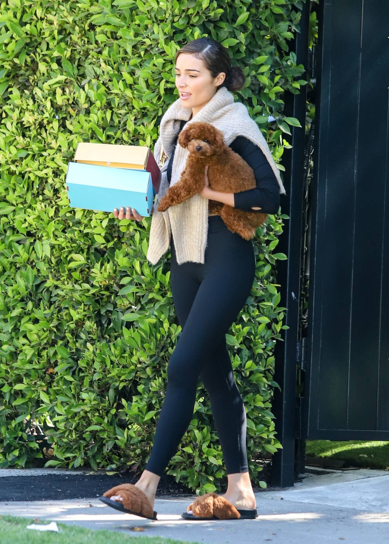 Olivia Culpo donning round brown faux fur slip on slippers with flat heel
