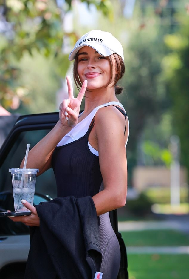 Olivia Culpo wearing brand logo white Adidas lace-up sneakers with flat heel