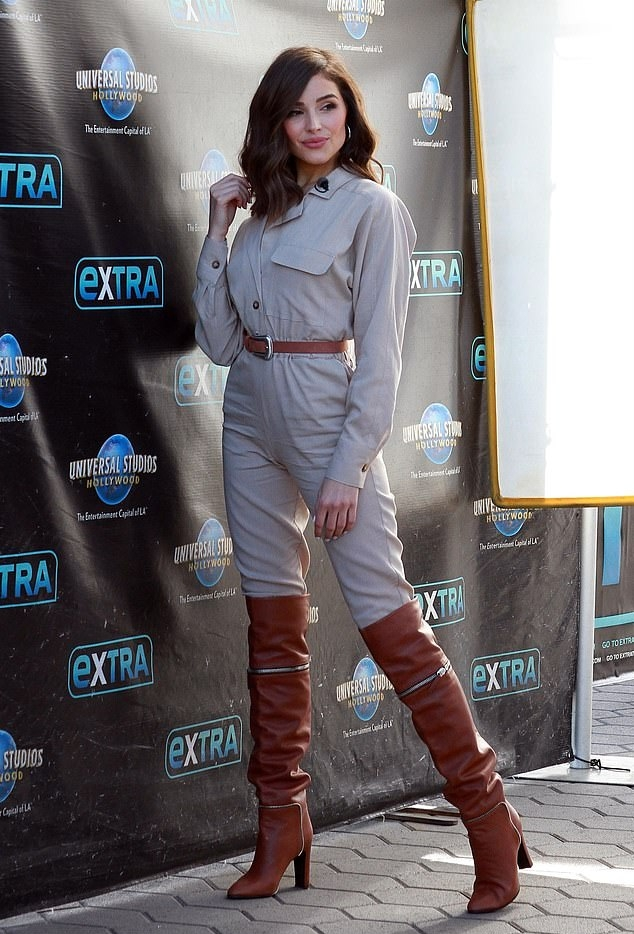 Olivia Culpo donning a straight fit beige jumpsuit with a crepe material, below elbow sleeves, peak lapel collar, button front and gathered waist