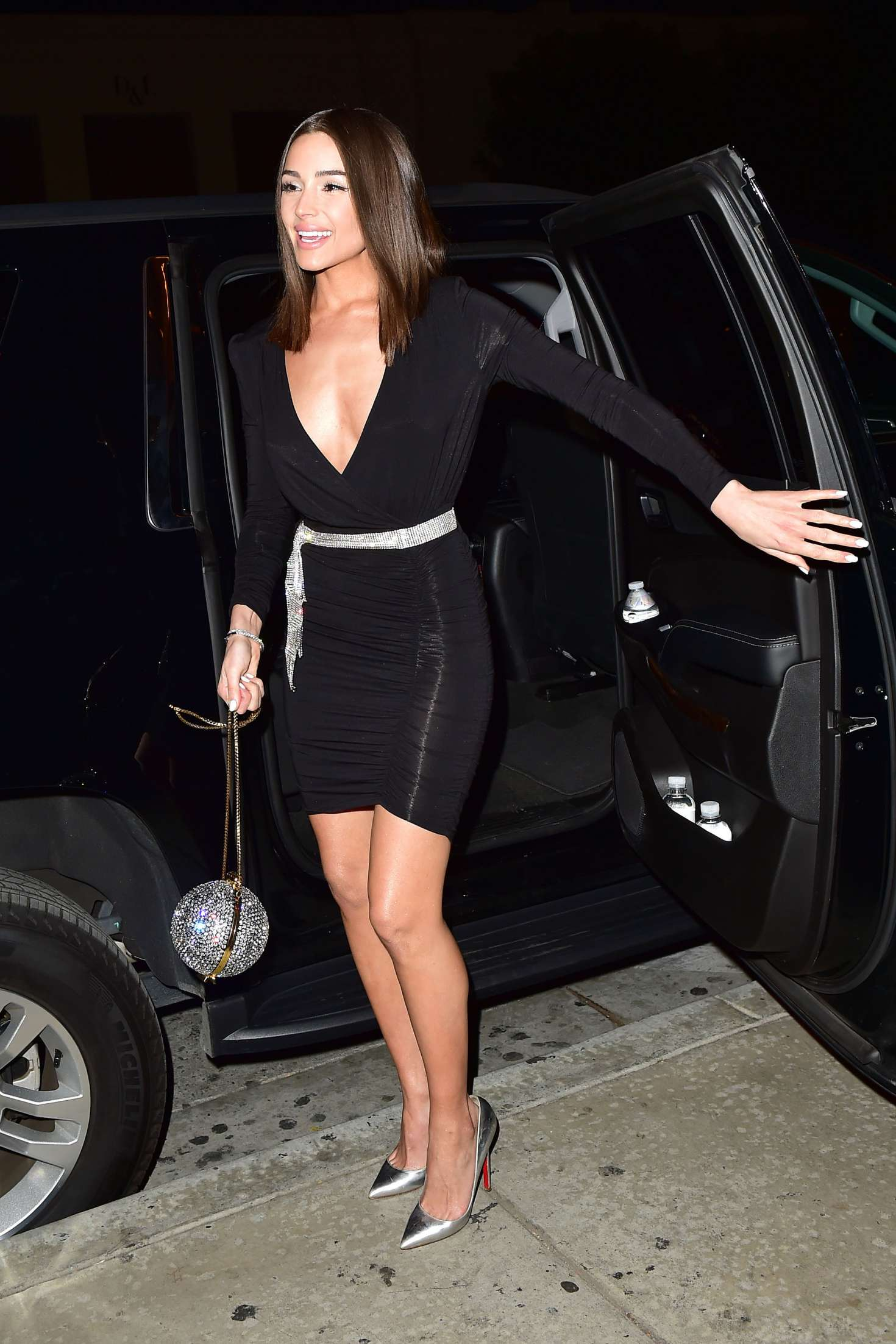 Olivia Culpo wearing a formfitting black dress with a polyester material, full sleeves, plunging neckline that almost went down to her waist and asymmetric hem