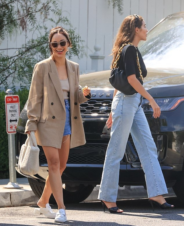 Olivia Culpo donning pointed black open toe sandals with high heel