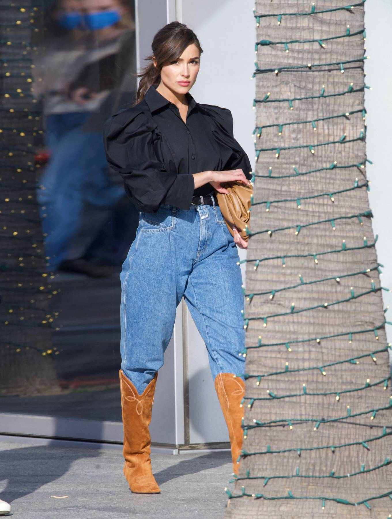 Olivia Culpo, brown boots, suede, oversized black blouse, Nude Bottega Veneta clutch, stitched, square, knee high, tan boots, blue jeans, heel, narrow, brown cowboy boots, kitten heel, tan cowboy boots. Olivia Culpo rocking stitched brown tan knee high cowboy boots with kitten heel