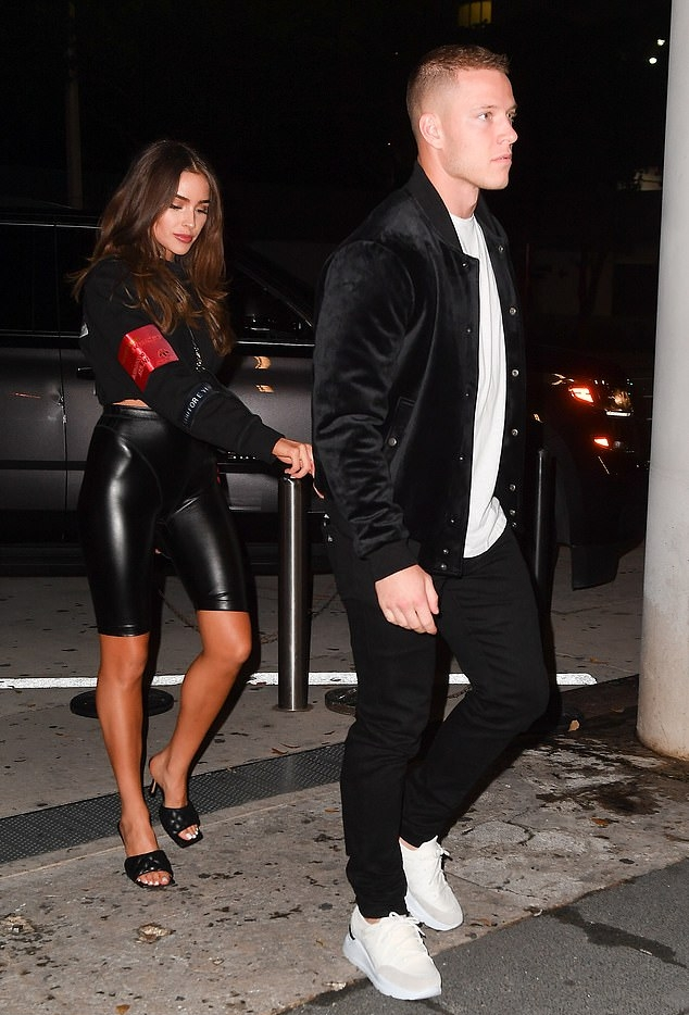 Olivia Culpo rocking a black cropped sweatshirt with full sleeves, patches and a crew neck