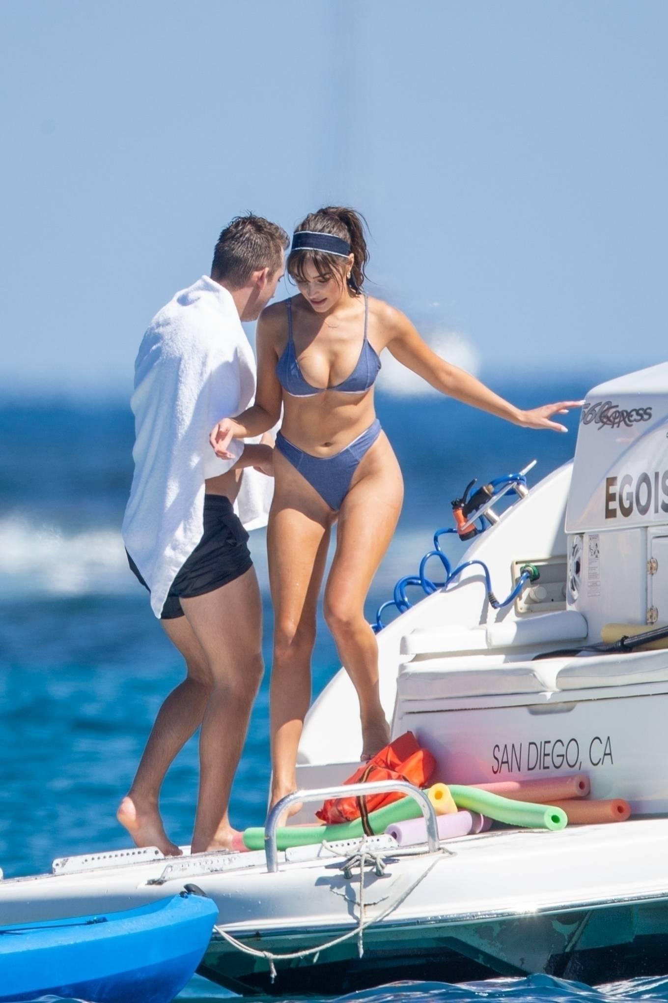 Olivia Culpo wearing a very low neck blue bikini top with spaghetti straps