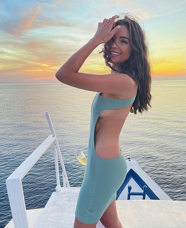 Olivia Culpo wearing a figure hugging blue dress with cut out and a round neck
