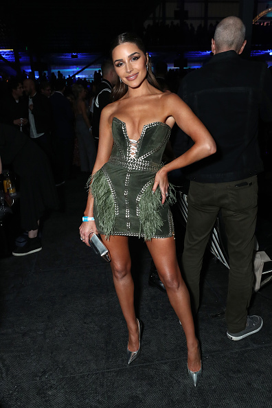 Olivia Culpo wearing a plunging emerald green dress with a luxe velvet material and chain detailing