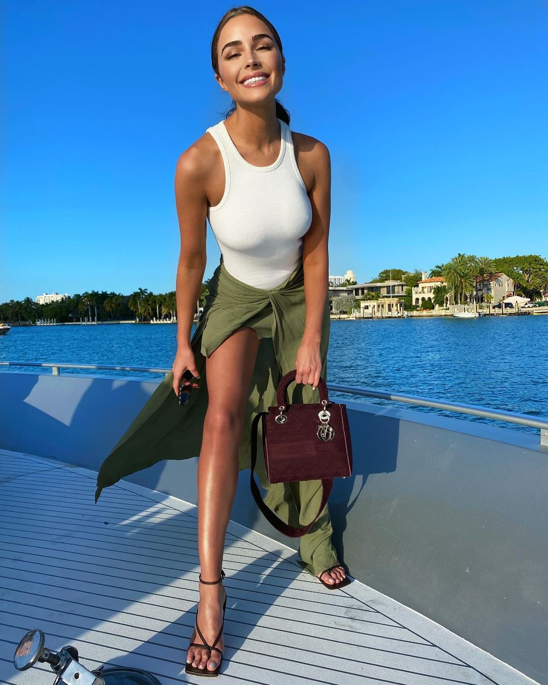 Olivia Culpo donning a military green draped flowing maxi skirt