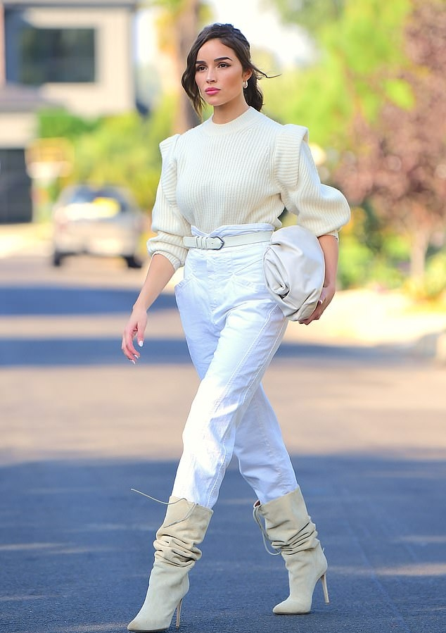 Olivia Culpo rocking pointy cream mid calf boots with pointy heel