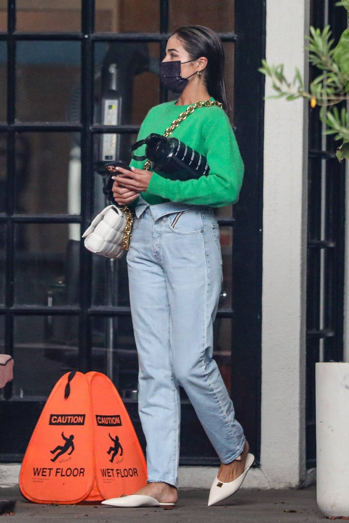 Olivia Culpo wearing a oversized green sweatshirt with full sleeves and a crew neck