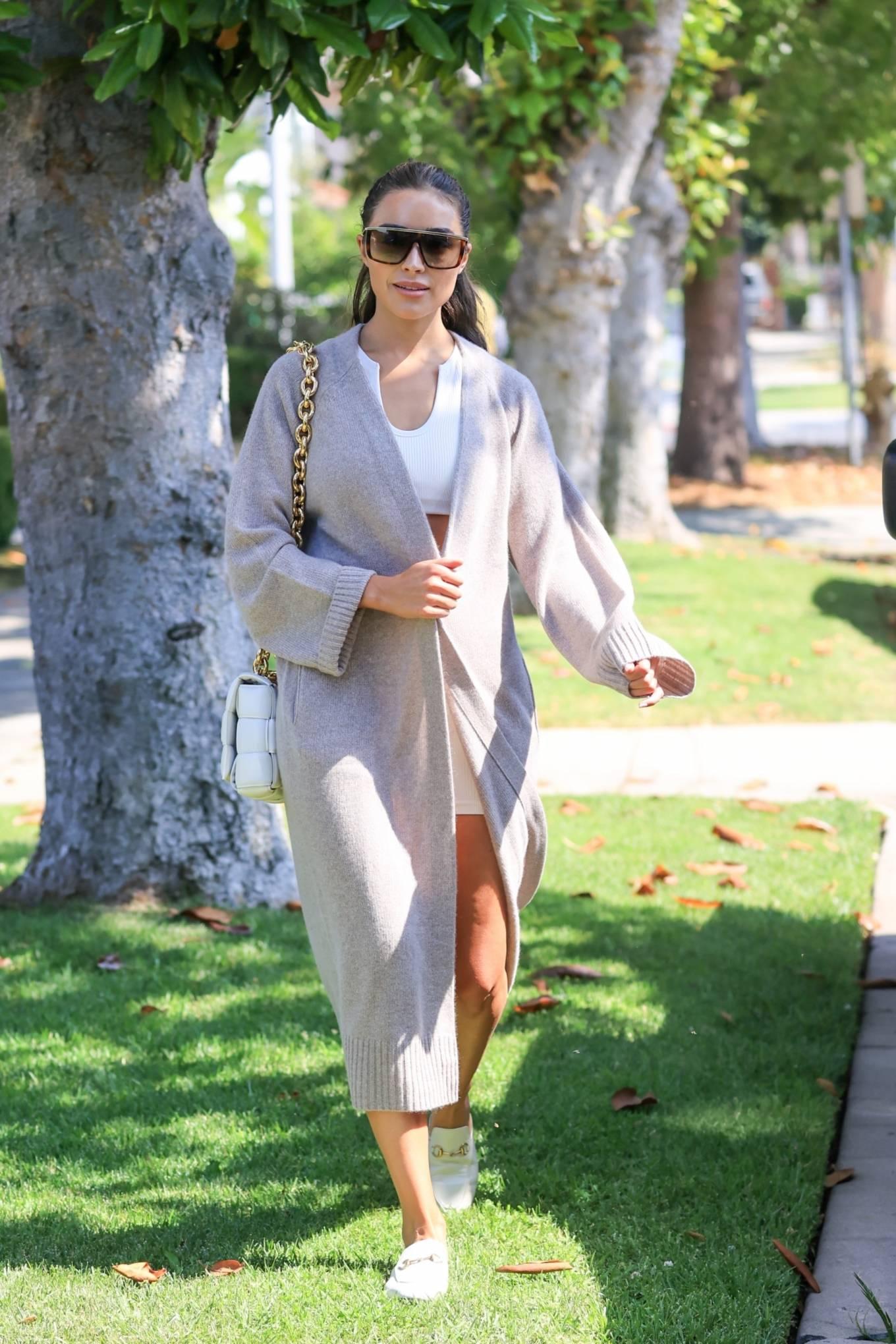 Olivia Culpo, white mules, oversized grey trench coat, white shoulder bag, round, white sports bra. Olivia Culpo rocking round white mules