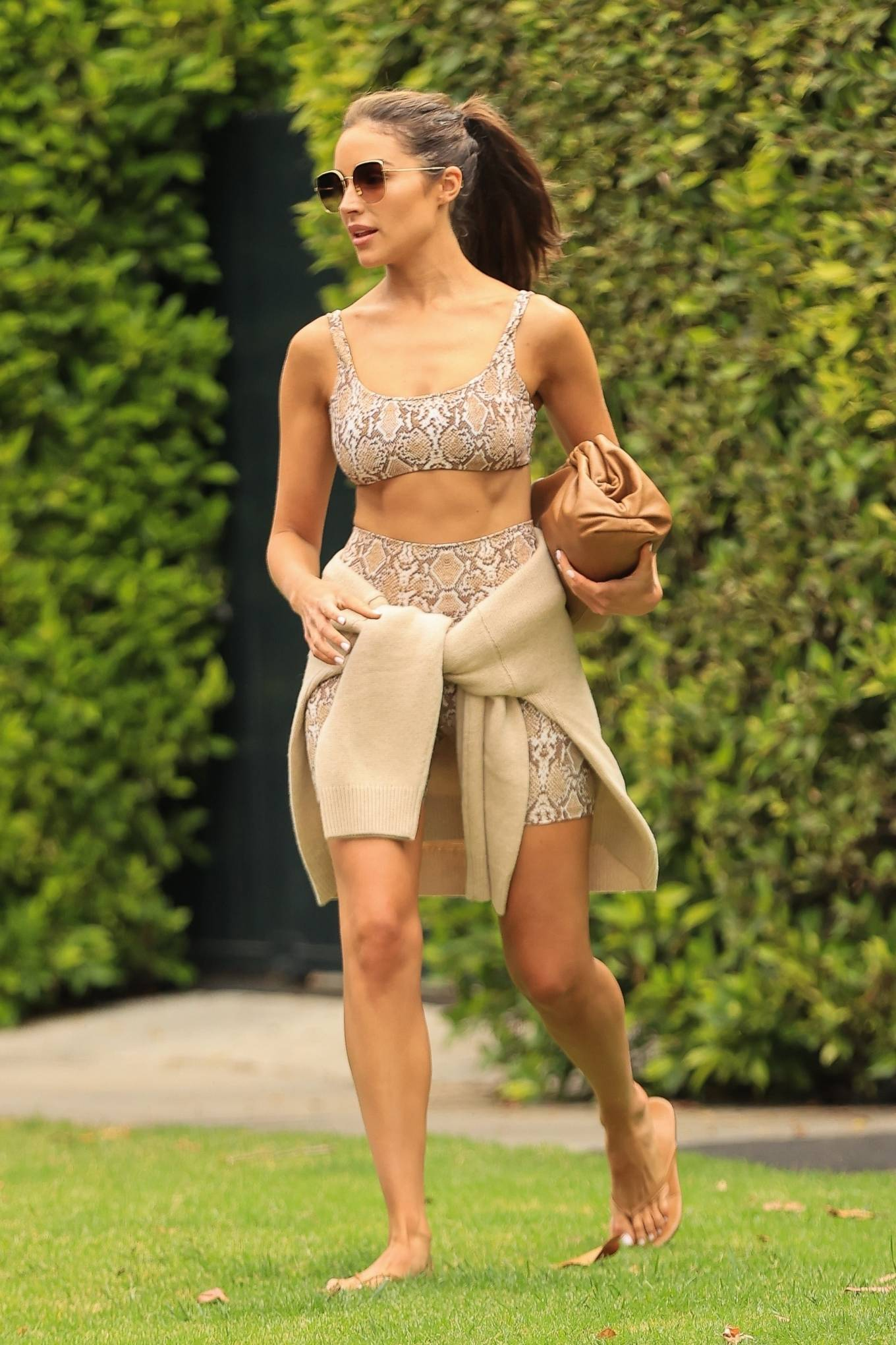 Olivia Culpo donning a fitted bikini top with pattern, a scoop neck and straps