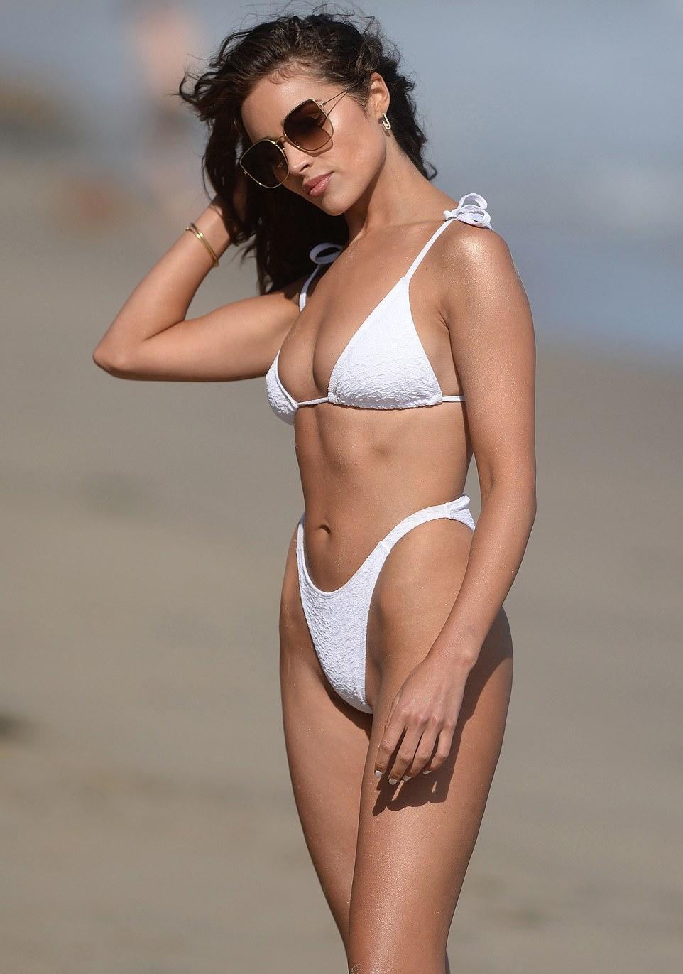 Olivia Culpo donning skimpy white low rise bikini bottom with creased detailing