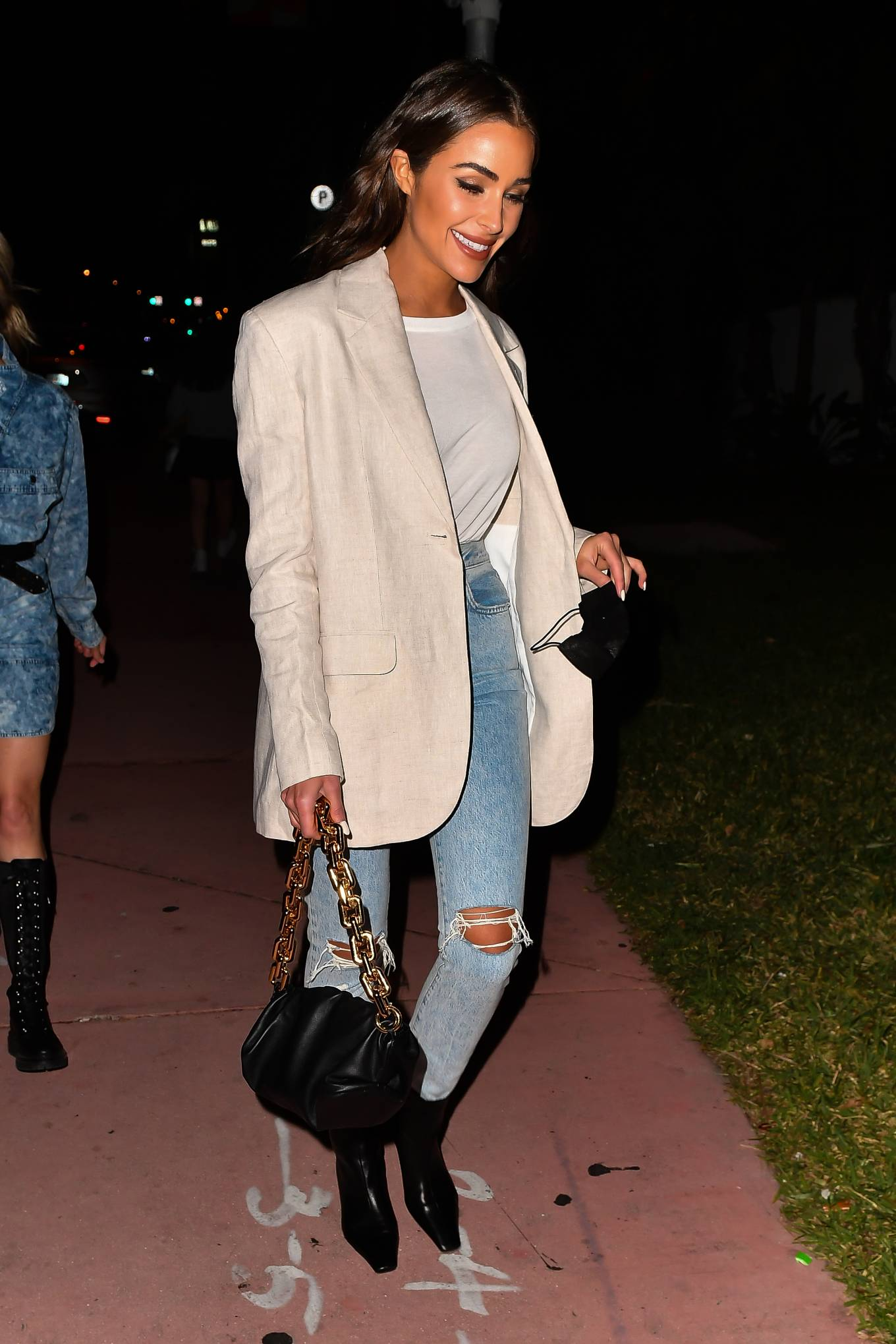 Olivia Culpo wearing narrow black leather ankle boots