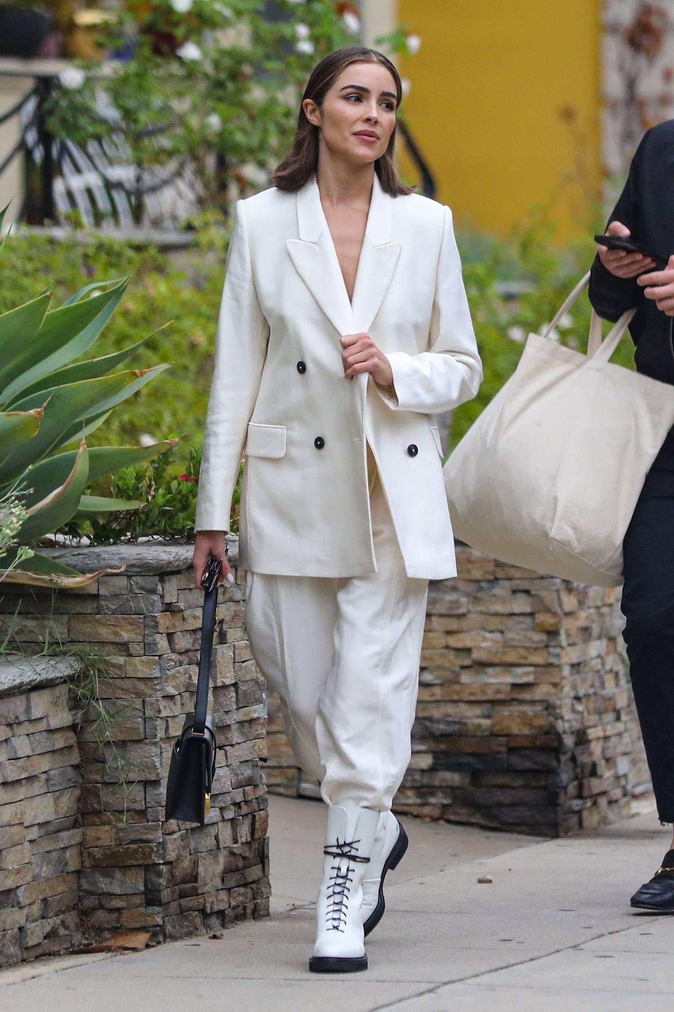 Olivia Culpo wearing cream trousers