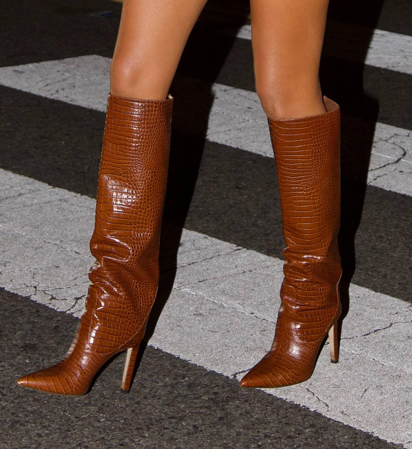 Olivia Culpo rocking sleek tan brown knee high boots by Jimmy Choo with high heel and Crocodile effect