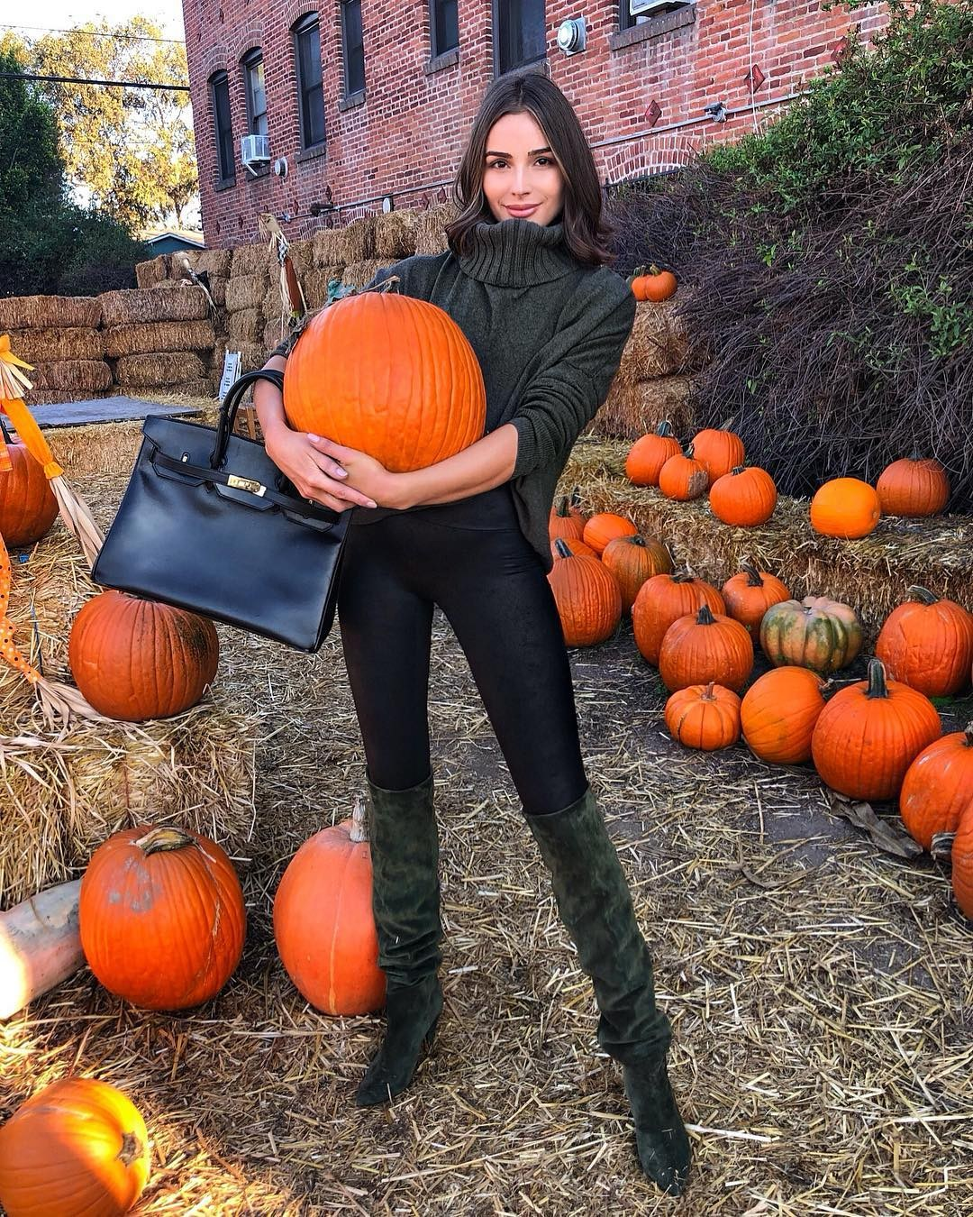 Olivia Culpo rocking black pants with a leather material