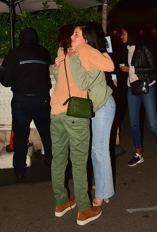 Olivia Munn wearing a oversized faded green sweatshirt with a woolen material, extra long sleeves and a crew neck